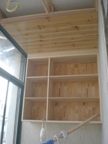 阳台上是用杉木集成板做成的吊顶,同时还做了个吊柜,以用作平时装放